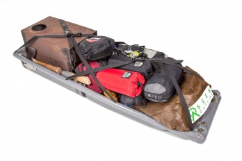 Snowclipper pulk loaded with camping gear including a Seek Outside 6 person tipi, Four Dog wood stove, pillow, Exped down mat, sleeping bag, water, cook set, food, extra clothes, saw, ax, shovel and a small camp chair.